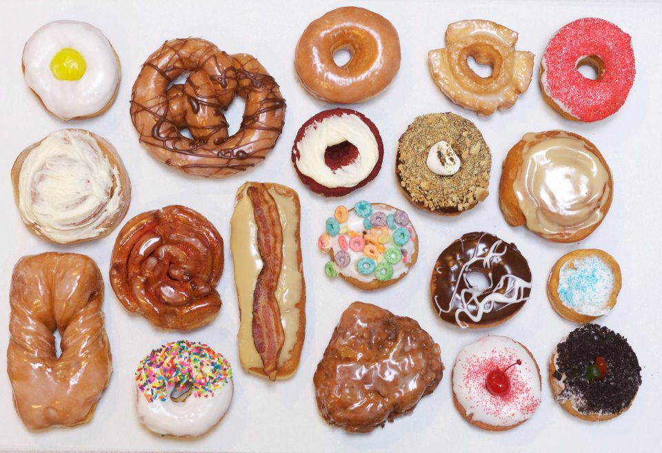 A wide selection of doughnuts, including all kinds of frosting and a bacon topped long john