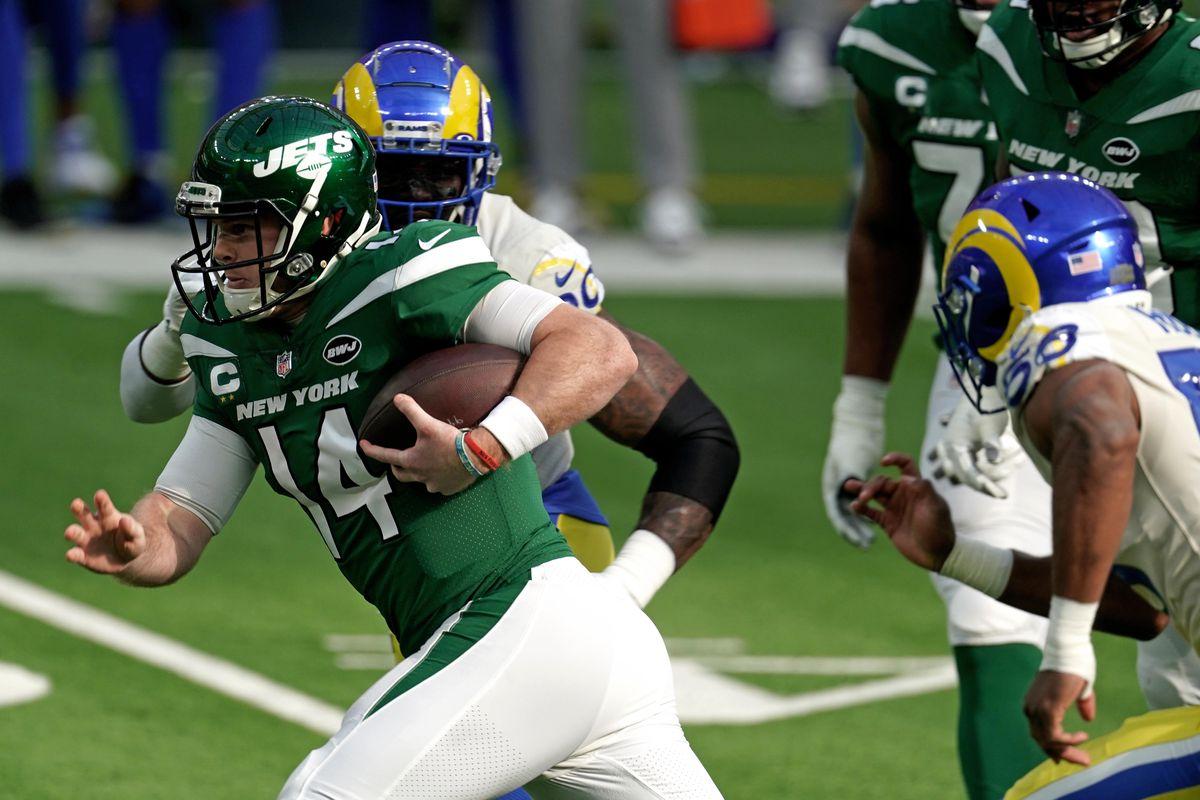 New York Jets quarterback Sam Darnold (14) carries the ball past Los Angeles Rams outside linebacker Samson Ebukam (50) during the first half at SoFi Stadium.