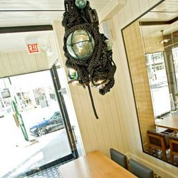 A hefty Japanese buoy-inspired chandelier hangs over the captain's table