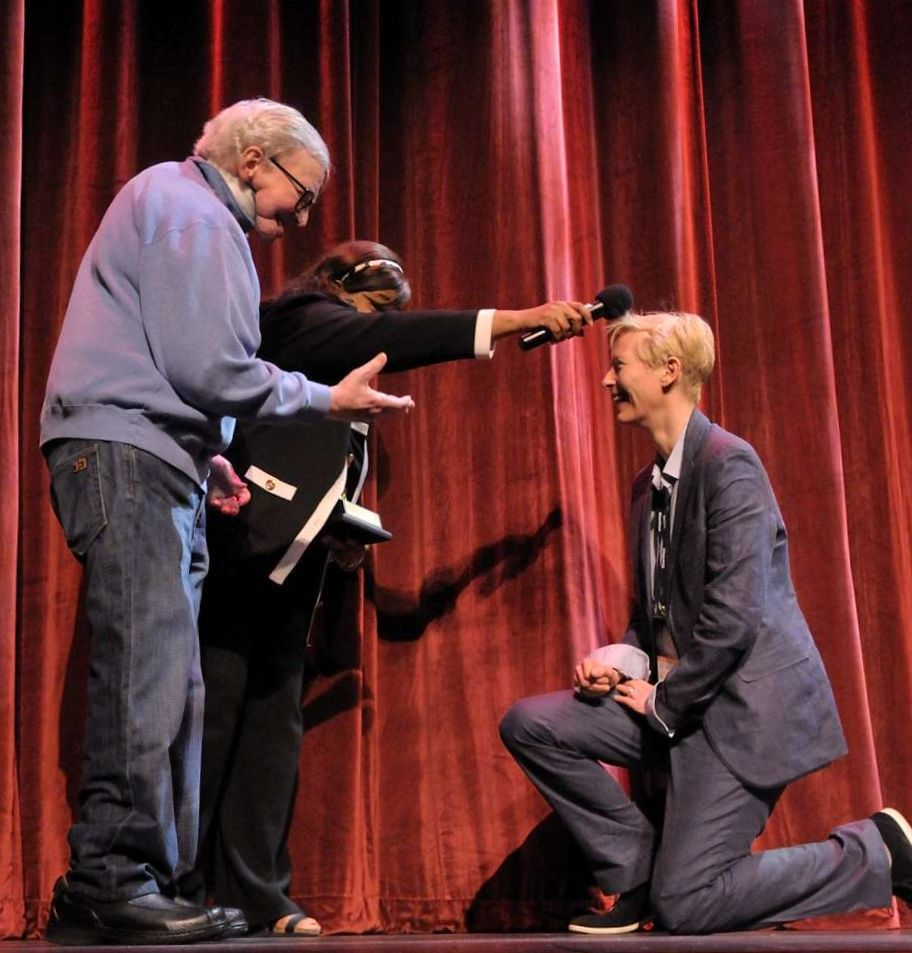 Actress Tilda Swinton (right) kneels before Roger and Chaz Ebert at Ebertfest 2011. | Thompson.McClellan