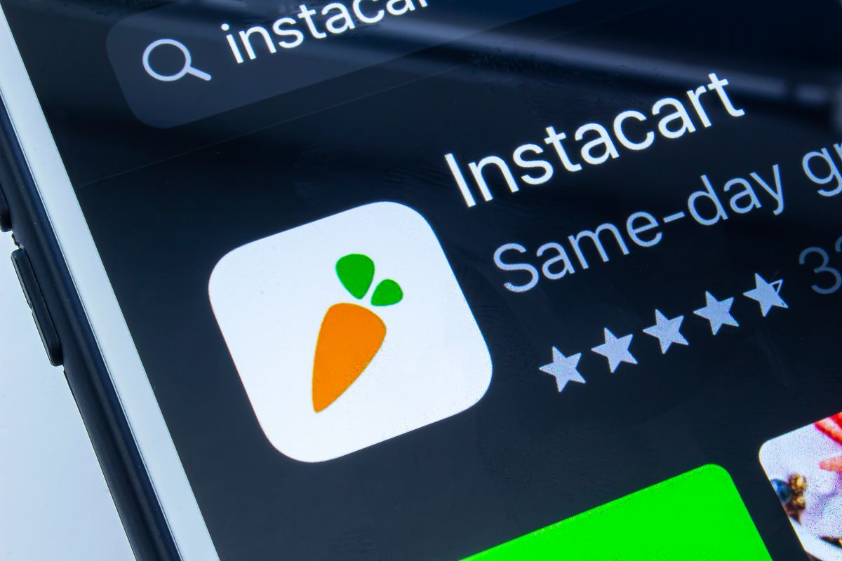 An iPhone displays the delivery app Instacart with its carrot icon