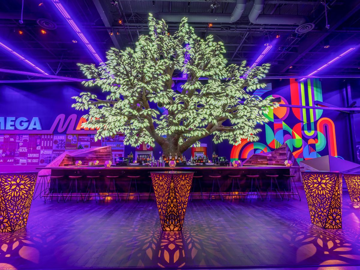 A tree piece of art surrounded by a bar and neon lights