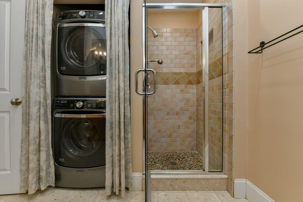 A shower with a glass door next to a stacked washer-dryer.
