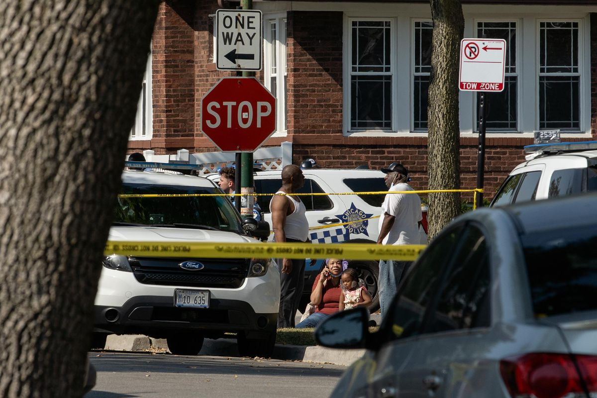 People sit on the street near the 1200 block of North Mason Avenue in the Austin neighborhood, where a person was fatally shot and two were injured, Friday morning, Oct. 1, 2021.