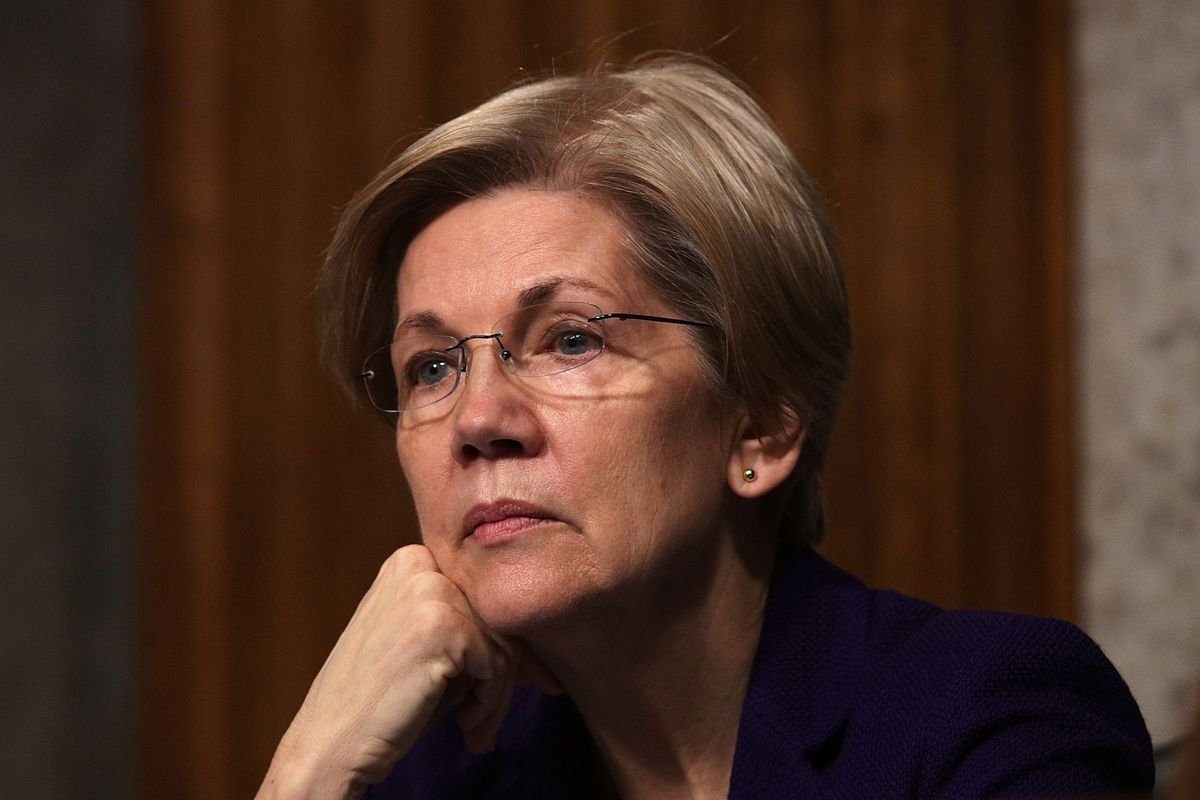 Senator Elizabeth Warren listens while resting her head on her right hand.