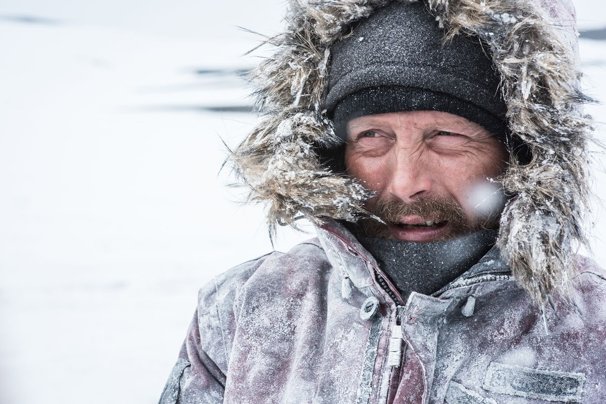 Mads Mikkelsen grimacing from the cold in Arctic.