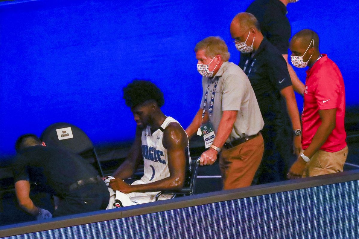 Jonathan Isaac of the Orlando Magic is helped off the court in a wheelchair after an injury against the Sacramento Kings in the second half of a NBA basketball game at HP Field House at ESPN Wide World Of Sports Complex on August 2, 2020 in Lake Buena Vista, Florida.