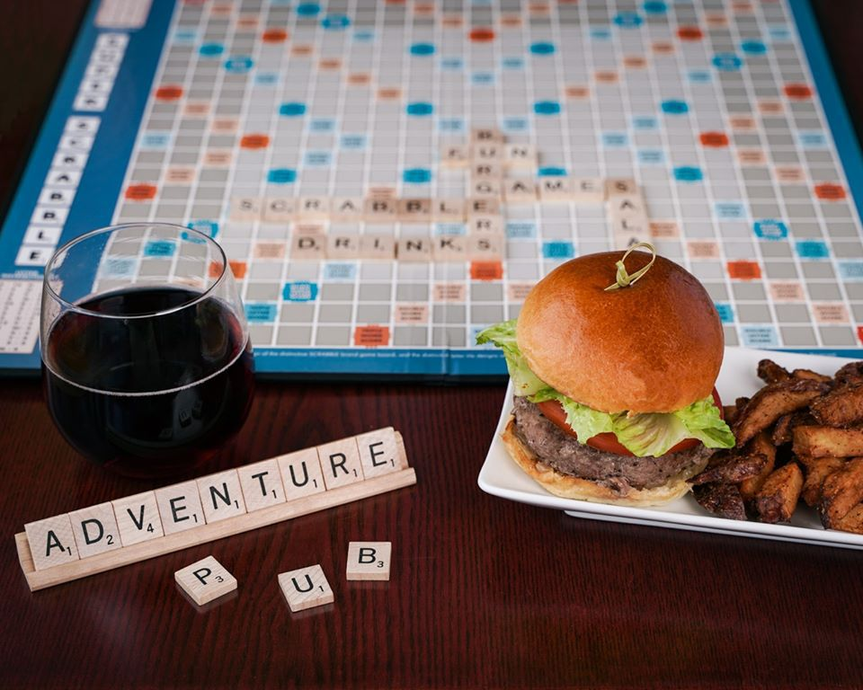 """A hamburger and glass of wine are displayed by a Scrabble board, which has words such as """"drinks,"""" """"games,"""" and """"burgers"""" on it. Tiles on the rack read """"Adventure Pub."""""""