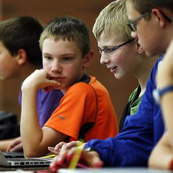 Jared Peck, center left, and Austin Oldroyd, center right, of Oquirrh Hills Middle School, work on computers as middle school students who have been involved in an after-school STEM program compete in West Jordan on Wednesday, May 27, 2015.