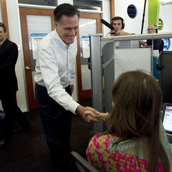 Republican presidential candidate, former Massachusetts Gov. Mitt Romney, center, greets a Google employee while touring the Chicago Google headquarters, in Chicago, Tuesday, March 20, 2012. Romney participated in a live-streaming internet discussion during the visit. (AP Photo/Steven Senne)