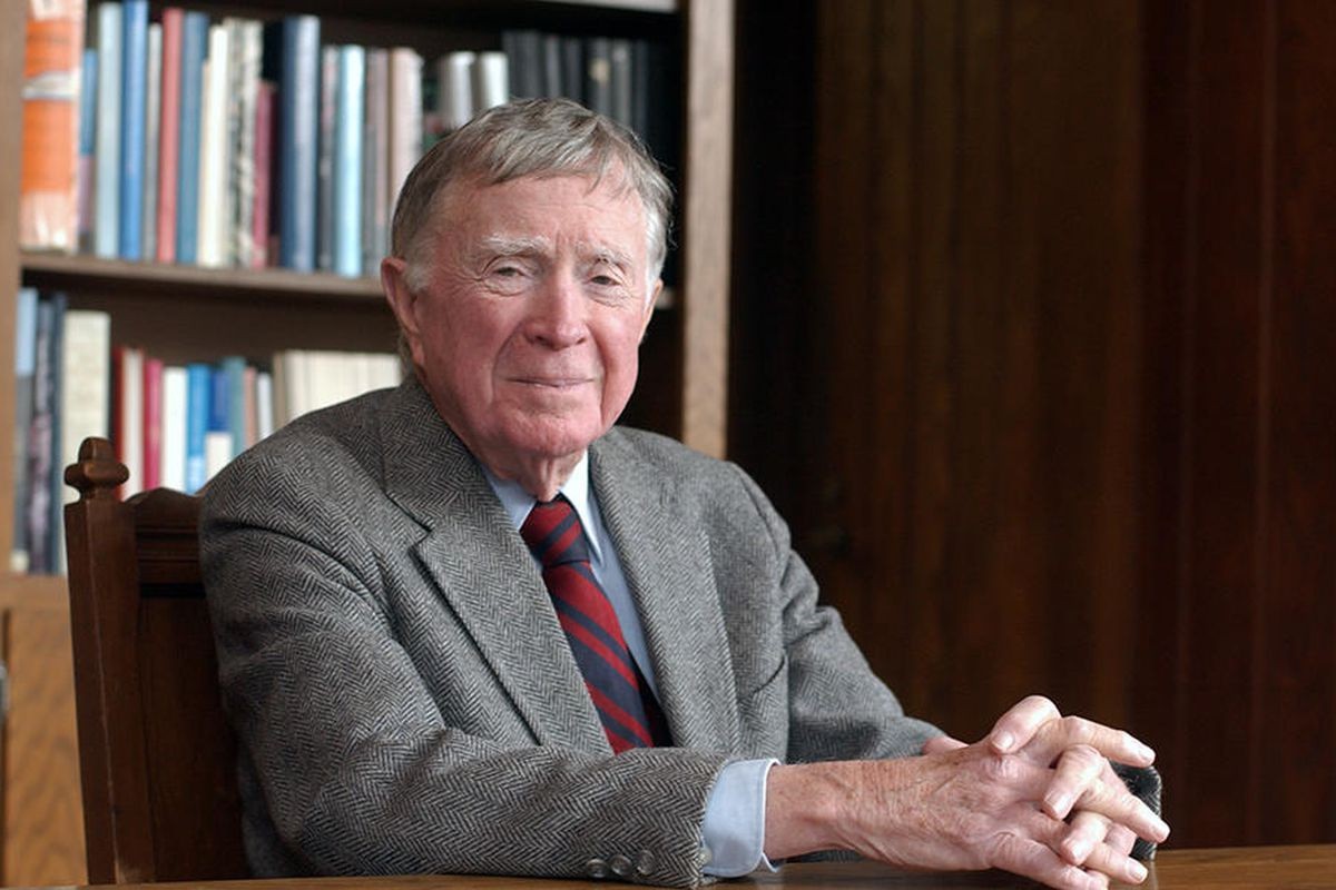 Photo of an elderly man with gray hair wearing a tweed jacket and tie sitting at a table with a bookshelf in the background.