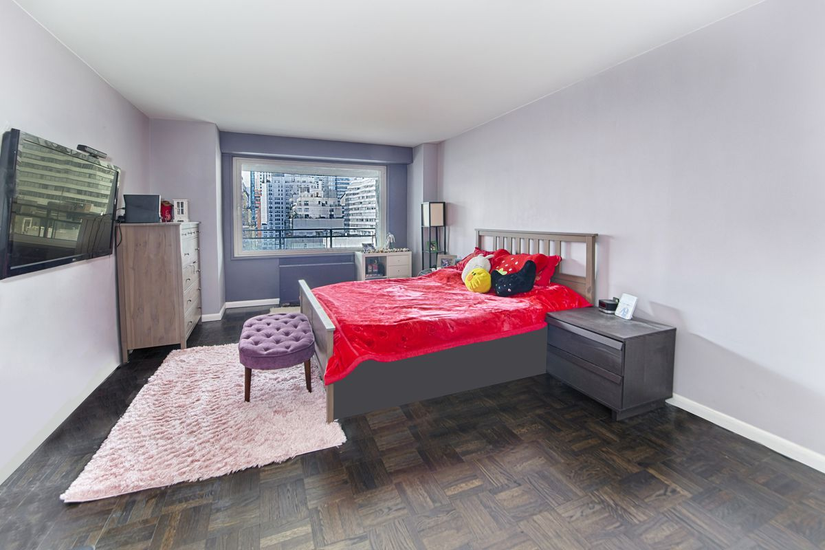 A bedroom with hardwood floors, a medium-sized bed, a pink rug, and light purple walls.