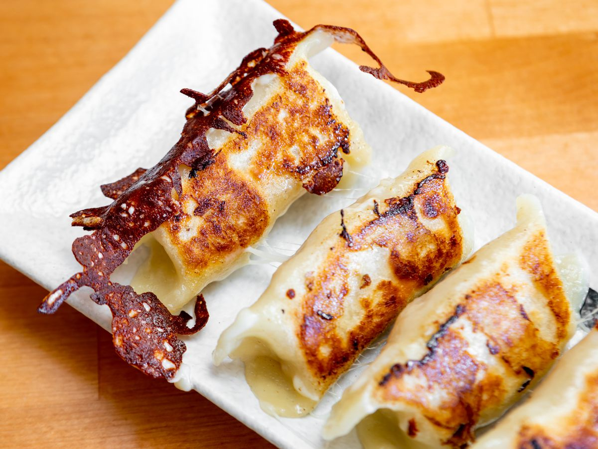 Plate of potstickers with crispy, browned cheese on the edges