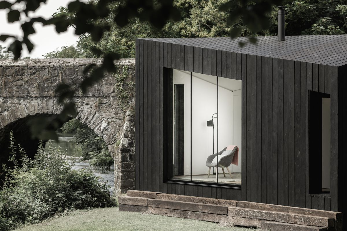 Exterior rendering of cabin with window and chair