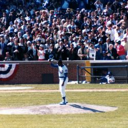 Ernie Banks, in full uniform, prepares to throw out a ceremonial first pitch. He tips his cap to the crowd...