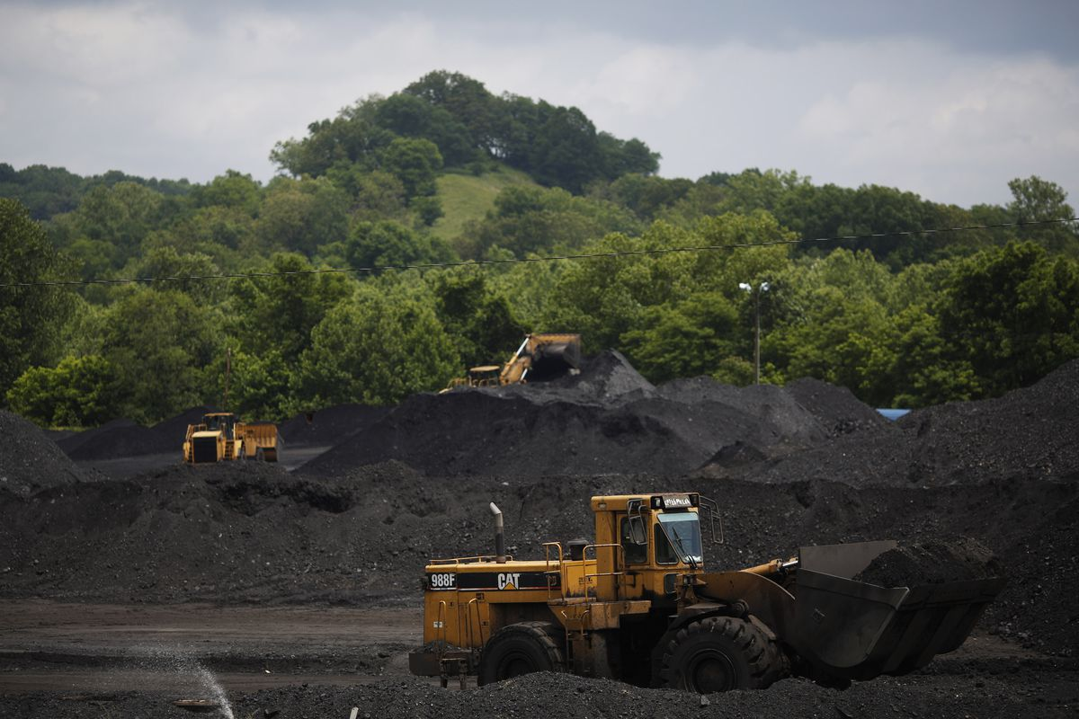 CATTLETSBURG, KY - JUNE 3: Caterpillar front-loading machinery operates on mounds of coal at Arch Coal Terminals June 3, 2014 in Cattletsburg, Kentucky. New regulations on carbon emissions proposed by the Obama administration have reportedly angered polit