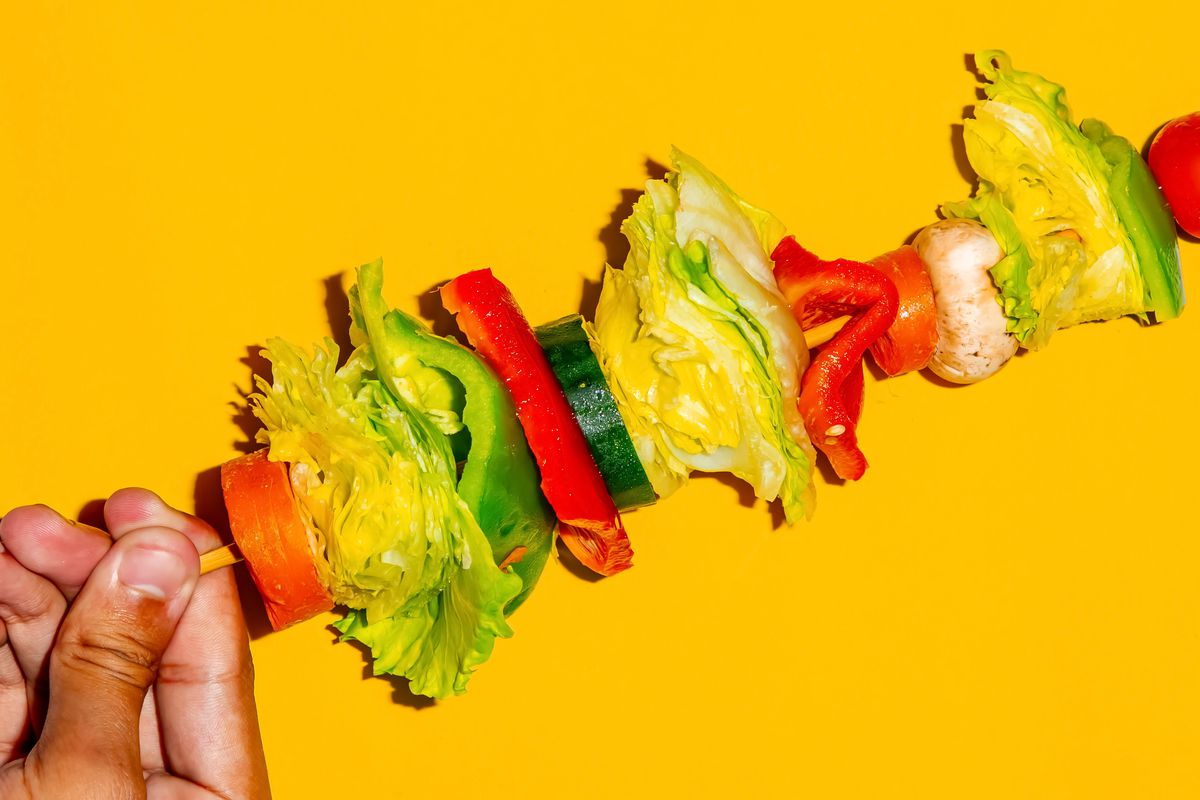 A hand holding a salad on a stick against a yellow background