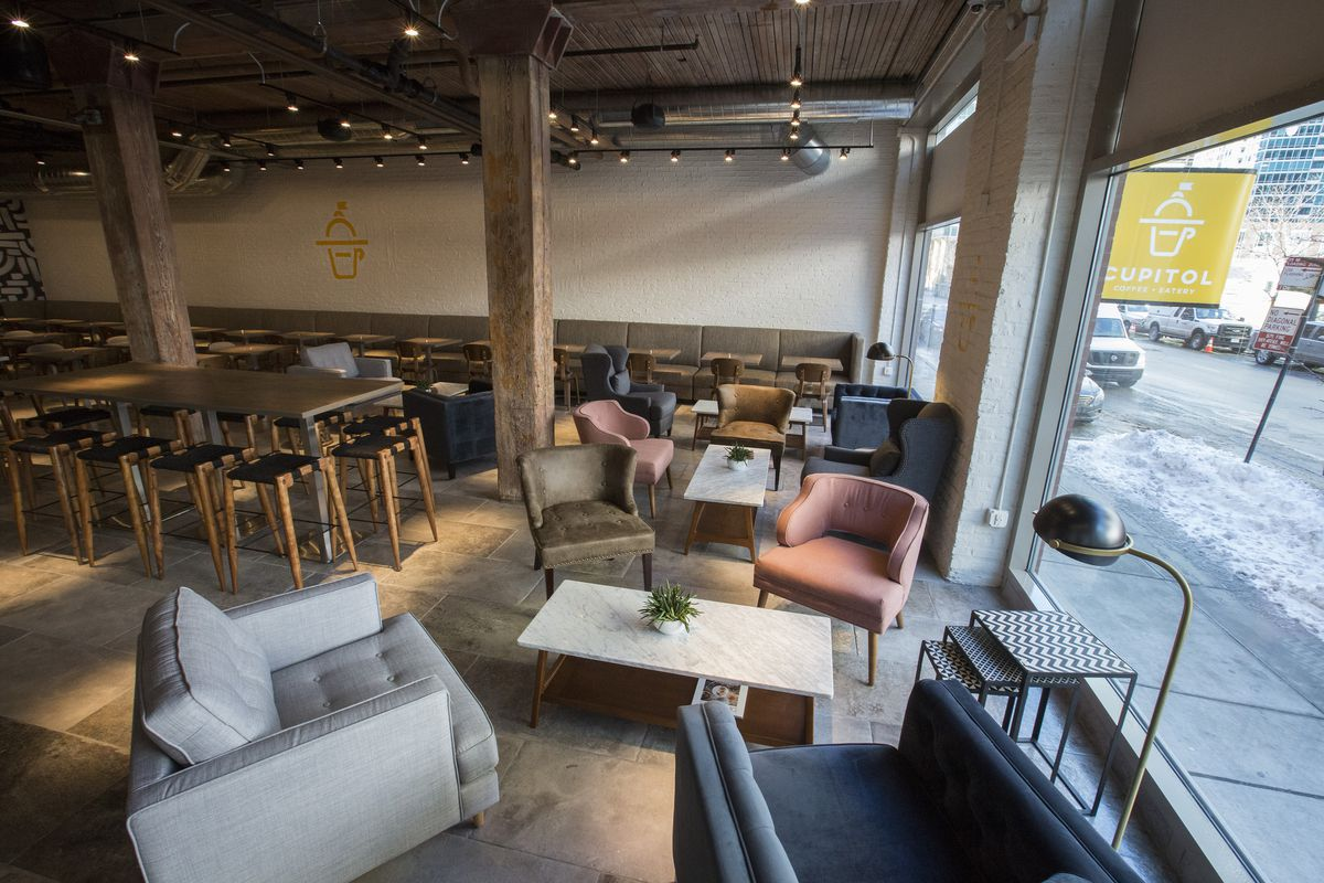 A spacious coffee shop with upholstered chairs around lounge tables.