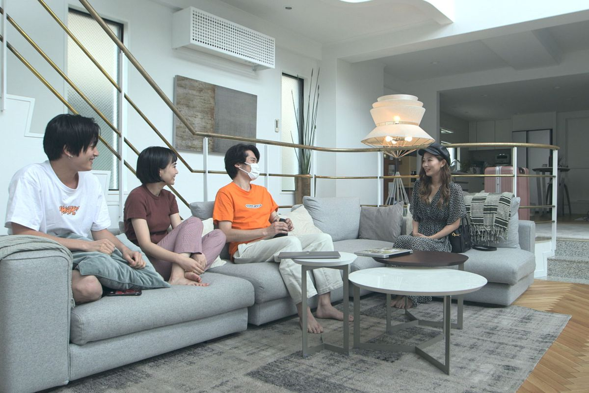Four people sit on a light grey couch in a communal living area in the Netflix series Terrace House Tokyo 2019 2020. There are white tables in front of the couch. In the background there is a lamp and a staircase with a metal bannister.