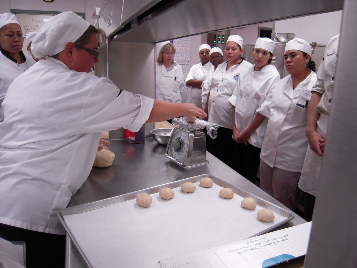 Sandy Grady, area supervisor for DPS Food and Nutrition Services, instructs boot camp students on how to make homemade hamburger buns of the proper weight and shape.