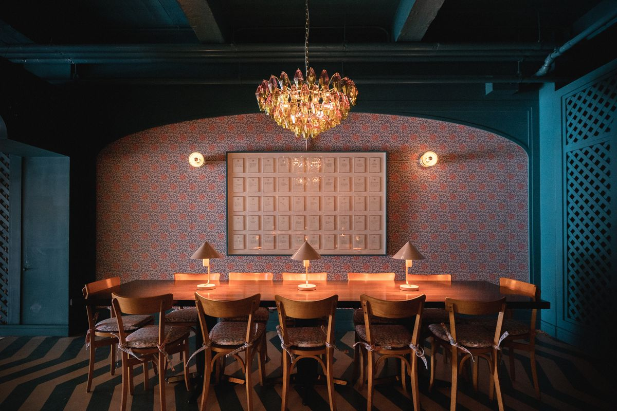 A communal table with bankers boxes on the far wall, custom light fixtures above them, and an ornate glass chandelier