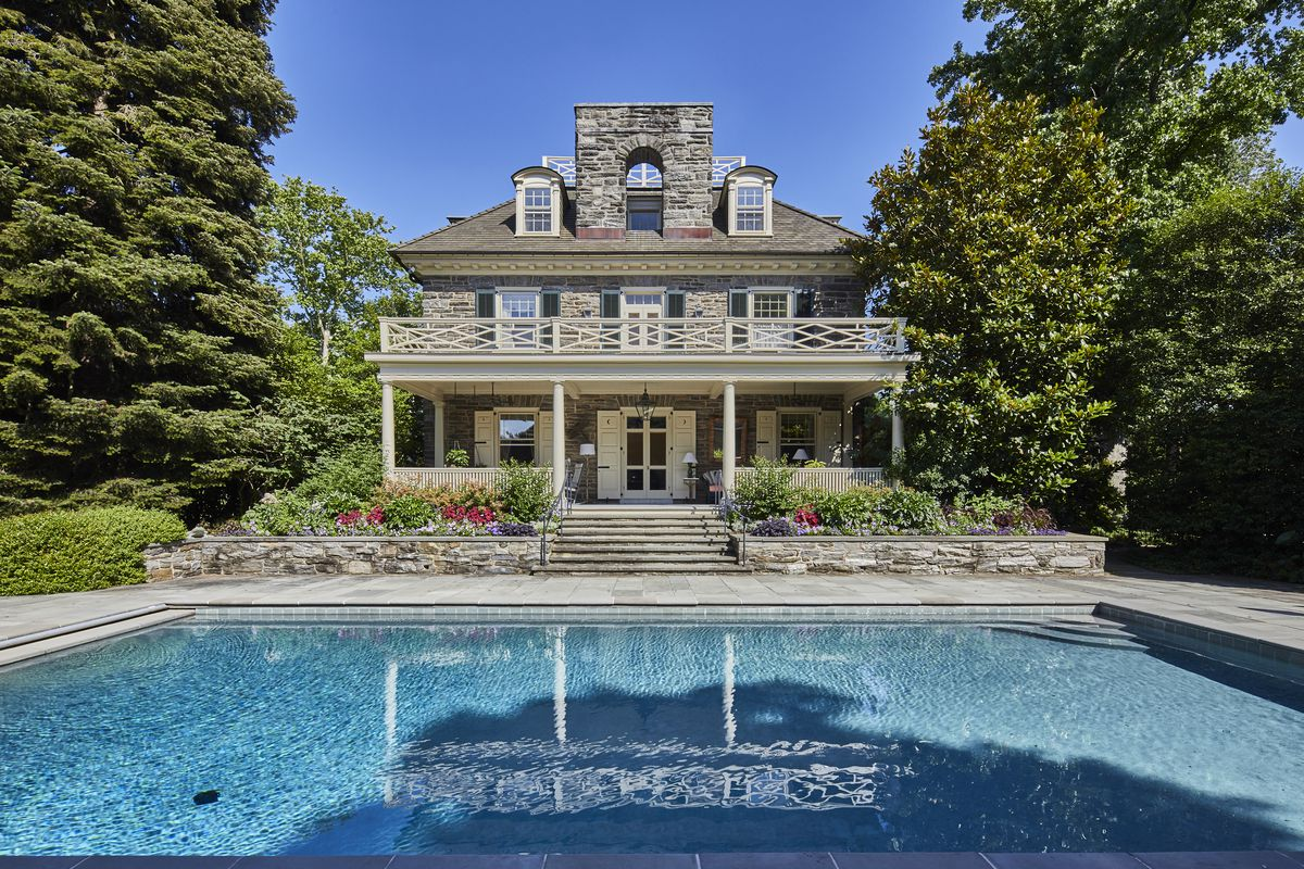 A pool sits in front of a pool house with stone and a second-story patio.
