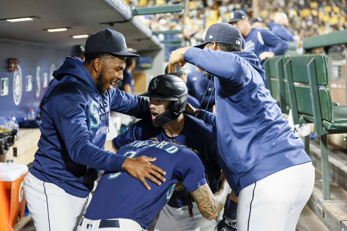 Mitch Haniger #17 of the Seattle Mariners reacts with Justin Dunn #35, J.P. Crawford #3 and Kyle Lewis #1 after Haniger's two run home run against the Los Angeles Angels during the fifth inning at T-Mobile Park on October 02, 2021 in Seattle, Washington.