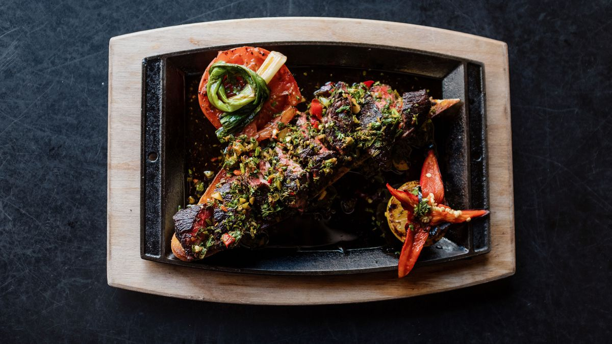 A thinly sliced hanger steak, grilled and drizzled with a bright green chimichurri, plated on a cast iron tray.