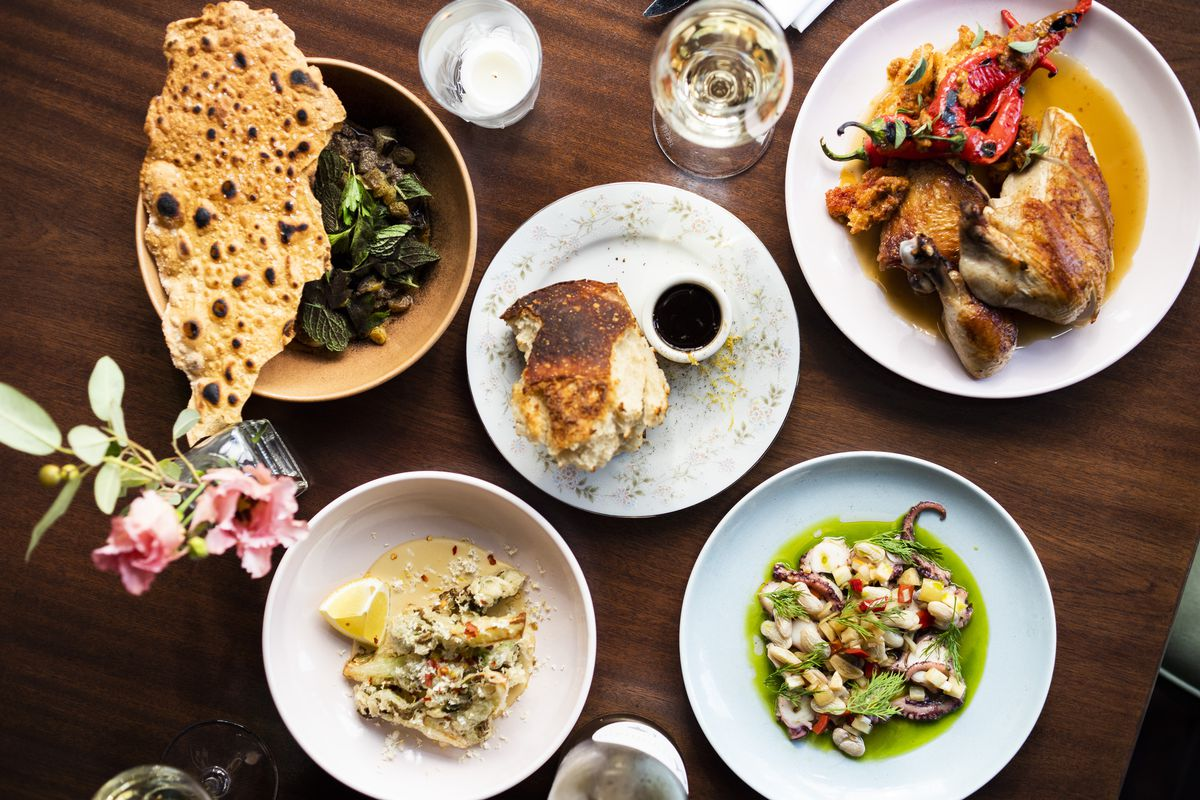 Clockwise from top: stewed eggplant, warm sourdough bread, roasted half chicken, octopus escabeche and fried squash at Income Tax Bar. | Provided photo by Income Tax
