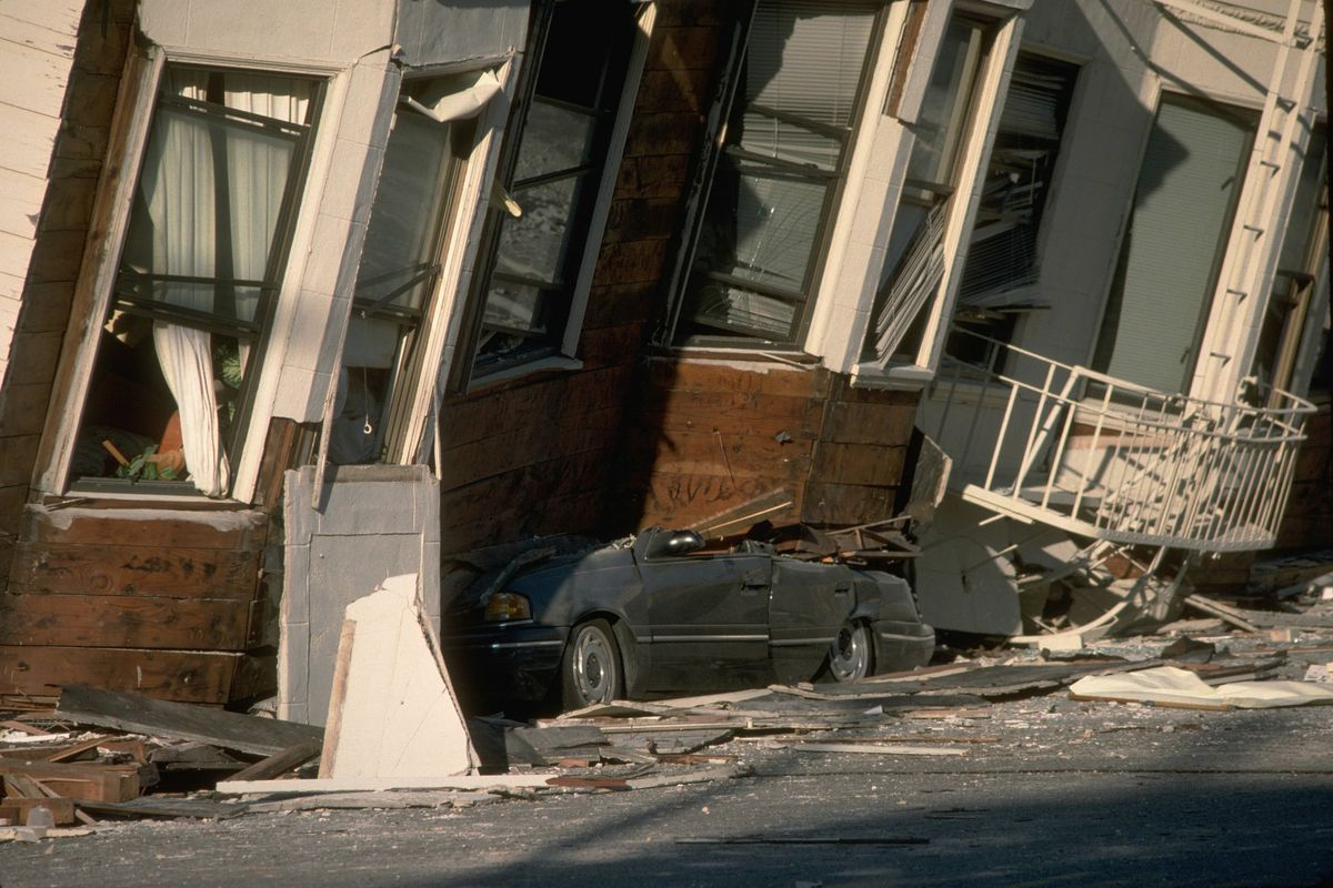 A car crushed underneath a partially collapsed building in the Marina.