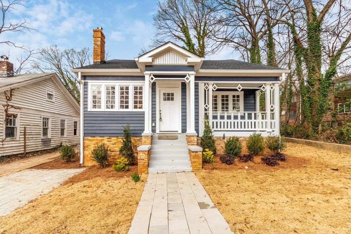 A small blue cottage with light brick and a charming front porch set back from yellow dormant grass.
