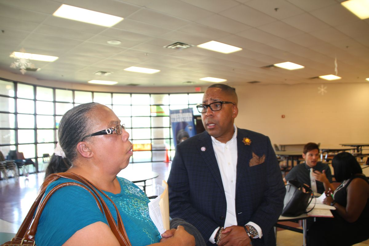 Rodney Rowan, assistant superintendent and new leader of the district's iZone, talks with his former colleague Sandra Jenkins at a job fair. Jenkins is looking for work after a car accident forced into early retirement several years ago.