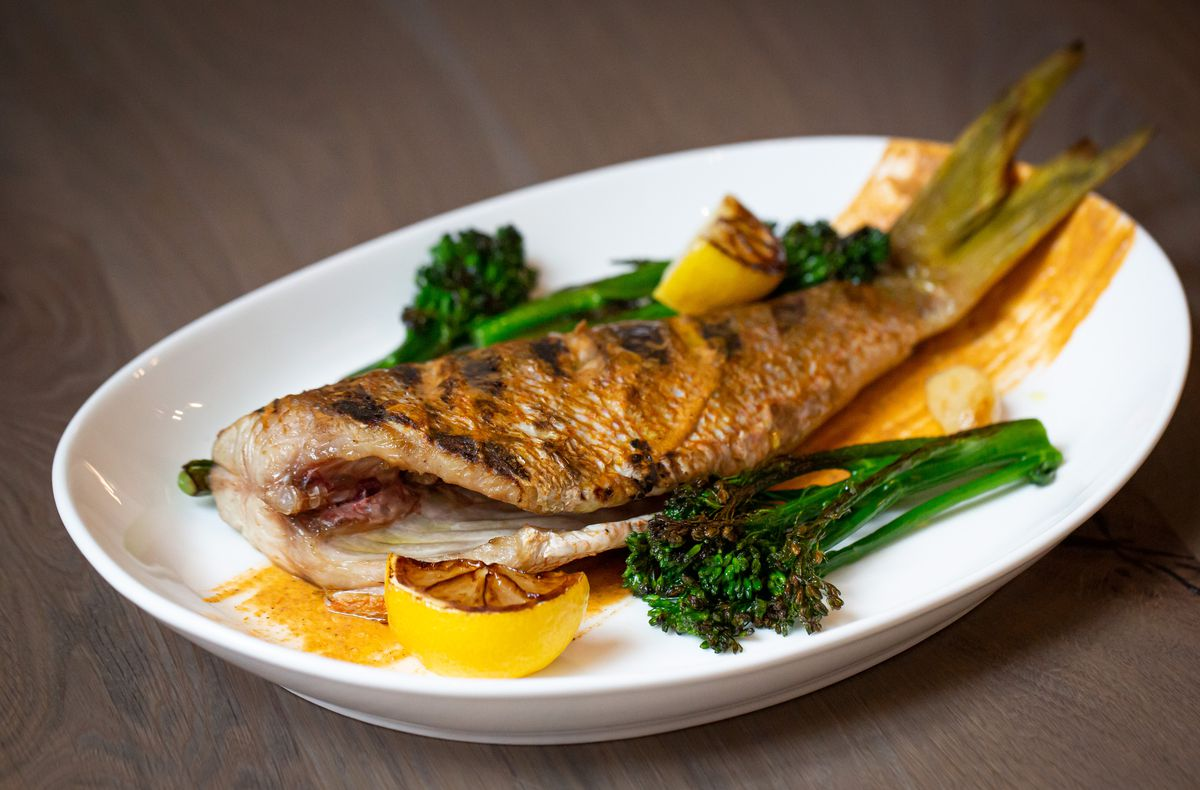 A whole roasted, bone-in fish on a platter with sweet potato puree and roasted broccolini