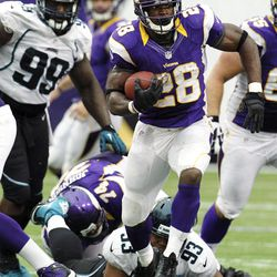 Minnesota Vikings running back Adrian Peterson rushes away from Jacksonville Jaguars defensive tackle C.J. Mosley (99) and defensive end Tyson Alualu (93) during overtime of an NFL football game, Sunday, Sept. 9, 2012, in Minneapolis. The Vikings won 26-23.
