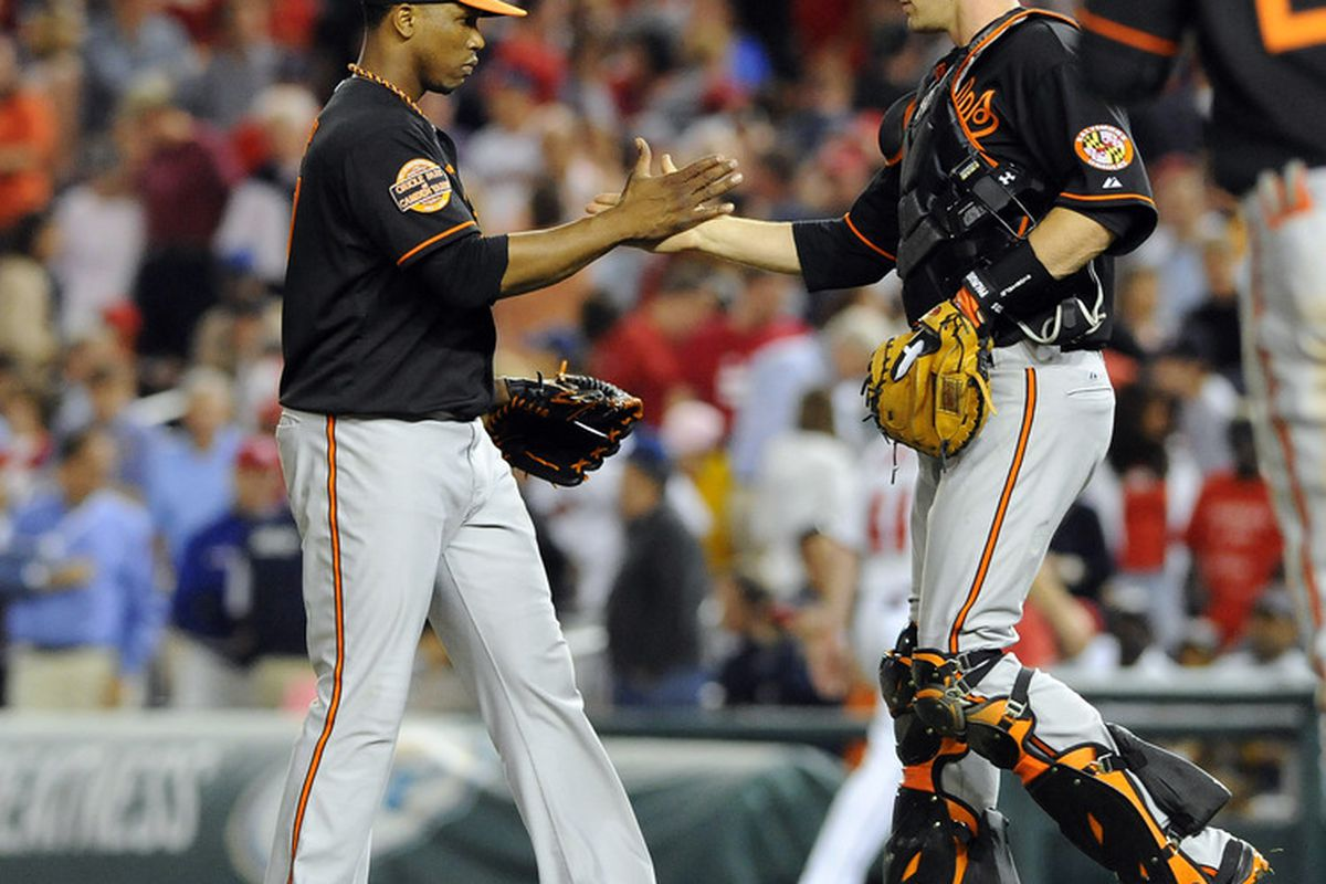 Baltimore Orioles relief pitcher Pedro Strop (47) is congratulated by catcher Matt Wieters (32) after earning a save against the Washington Nationals at Nationals Park Friday. Mandatory Credit: Brad Mills-US PRESSWIRE