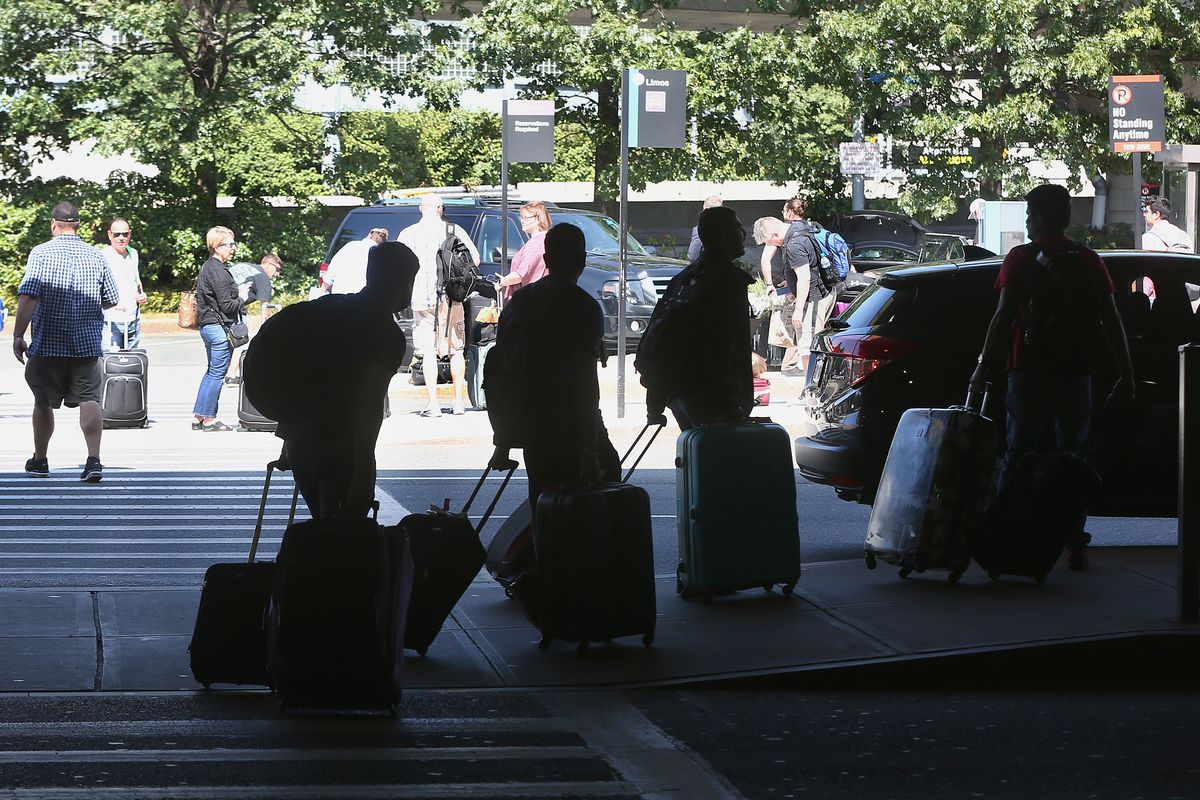 People rolling suitcases behind them as they emerge from cars at the airport.