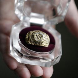 """Rulon Gardner's Olympic gold medalist ring is shown at Erkelens & Olsen Auctioneers Friday, Oct. 19, 2012, in Salt Lake City. The auction of Olympic gold medalist Rulon Gardner's most valuable belongings is being postponed indefinitely as the decorated wrestler tries to buy back """"stuff that really matters to him,"""" his new bankruptcy lawyer says. A major creditor seized a Ford Excursion SUV, Harley-Davidson motorcycle, dozens of watches and knives, his wrestling shoes, autographed memorabilia and more. Gardner's gold and bronze medals are not in play; he previously put them up as collateral for personal loans. (AP Photo/Rick Bowmer)"""