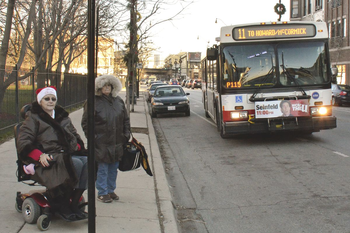 A Chicago Transit Authority bus approaches a bus stop to pick up passengers.