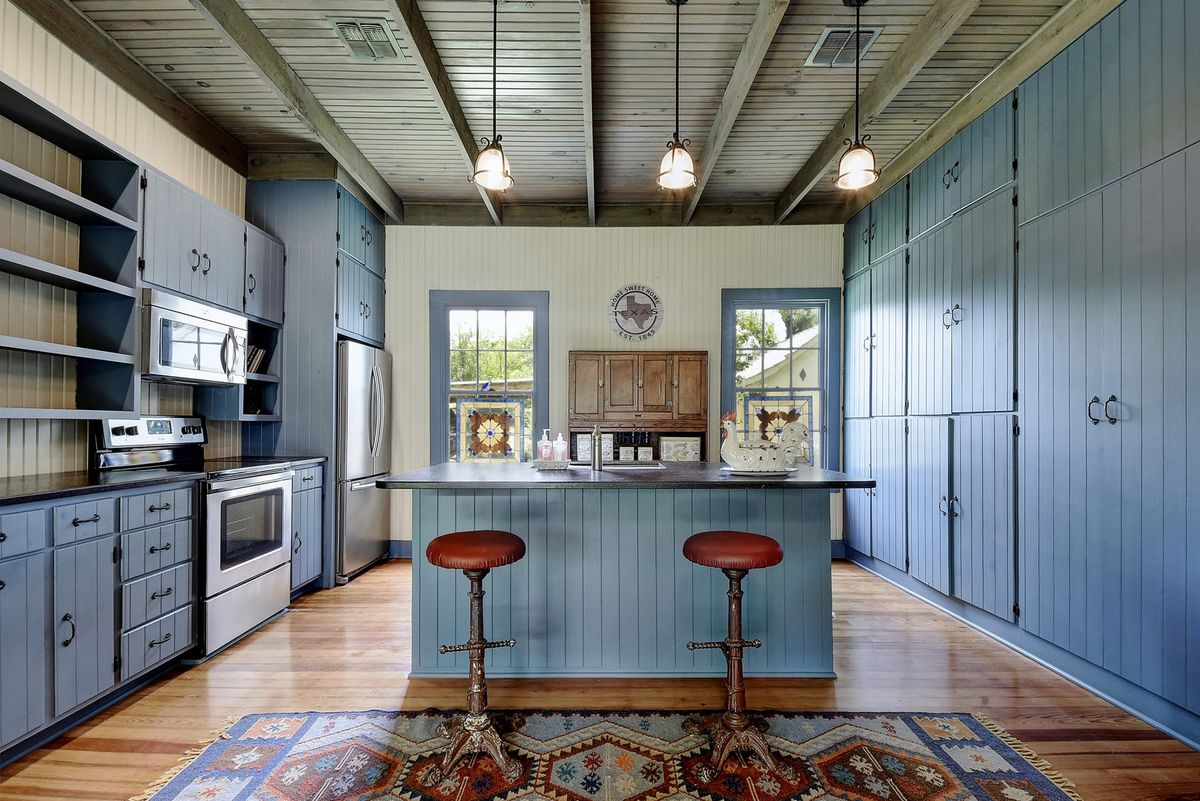 A kitchen has a large island, blue cabinets, and two bar stools.