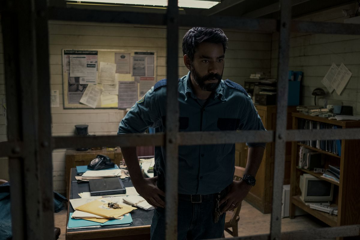 Rahul Kohli as Sheriff Hassan looking out a window in Midnight Mass.