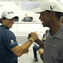 Rory McIlroy of Northern Ireland, left, shakes with Tiger Woods between interviews during the Pro-Am of the BMW Championship PGA golf tournament at Crooked Stick Golf Club in Carmel, Ind., Wednesday, Sept. 5, 2012.