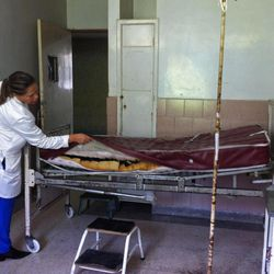 In this Oct. 23, 2013 photo, a doctor pulls up a mattress cover to show the condition of a hospital bed's cushion, at the Central Hospital in Maracay,Venezuela.