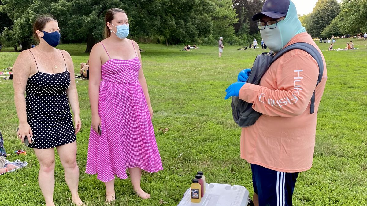 A man in a face mask stands in front of a cooler containing drinks, two women are waiting in front to buy beverages