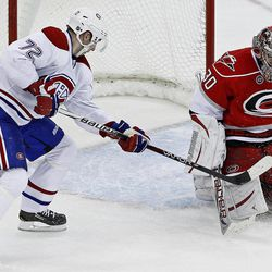 Carolina Hurricanes goalie Cam Ward (30) deflects a shot by Montreal Canadiens' Erik Cole (72) during the third period of an NHL hockey game in Raleigh, N.C., Thursday, April 5, 2012. Carolina won 2-1 in a shootout.