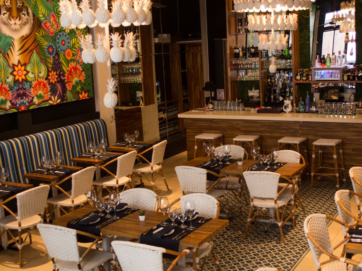 A dining room marked by chandeliers with pineapple-shaped lights, a large illustration of a tiger in a jungle on one wall, wooden patio chairs with woven backs, a patterned banquet along one wall, and a large bar with a mirror on the back bar