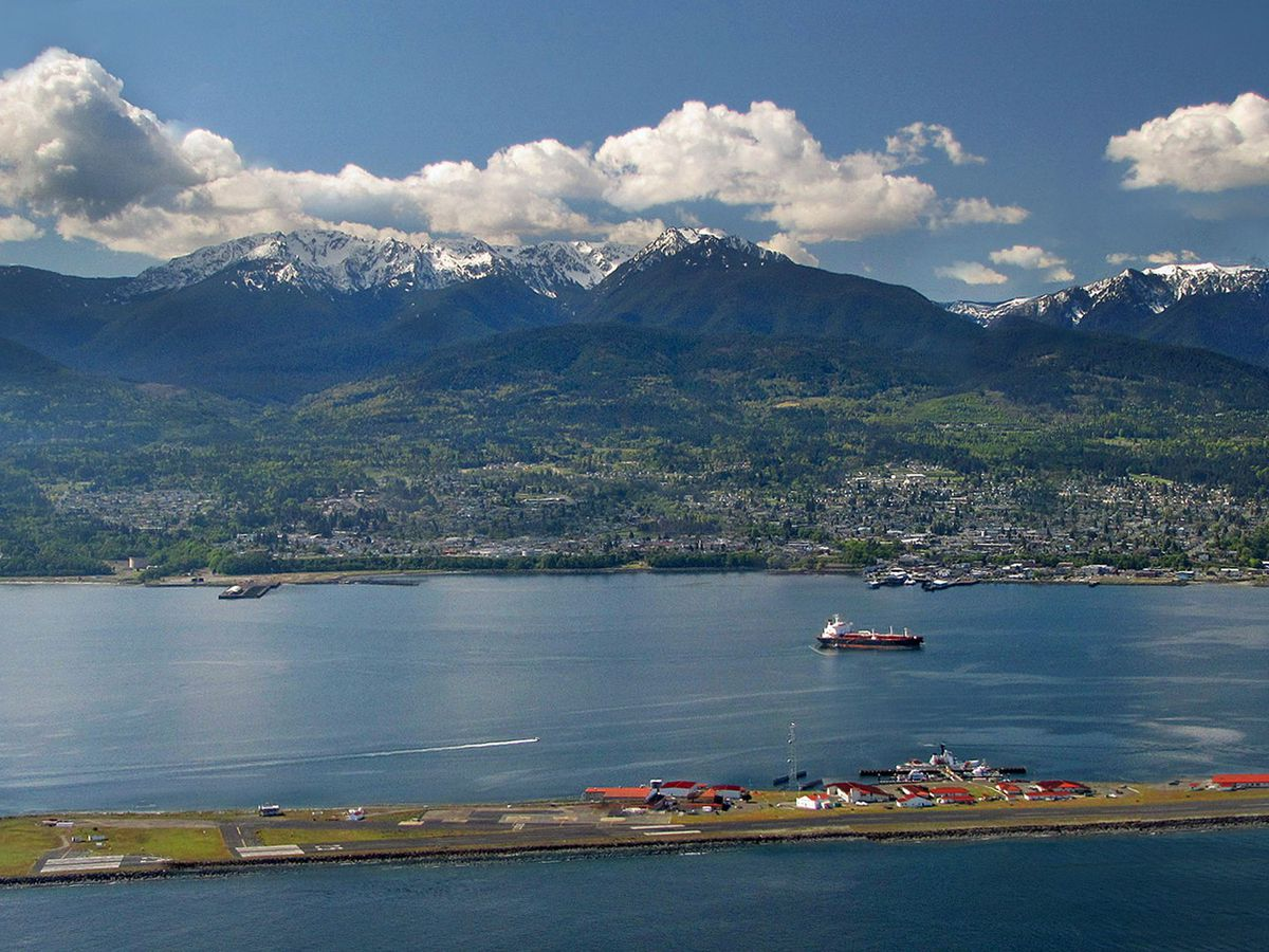 A body of water in Port Angeles near Seattle. There is a boat on the water. In the distance are mountains and clouds.