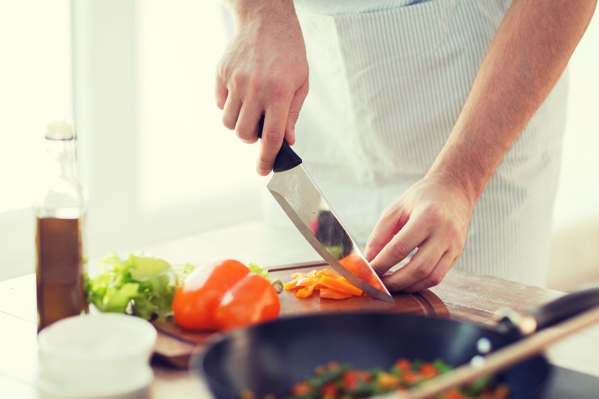A chef uses a knife to cut carrots, with a pan in the foreground.