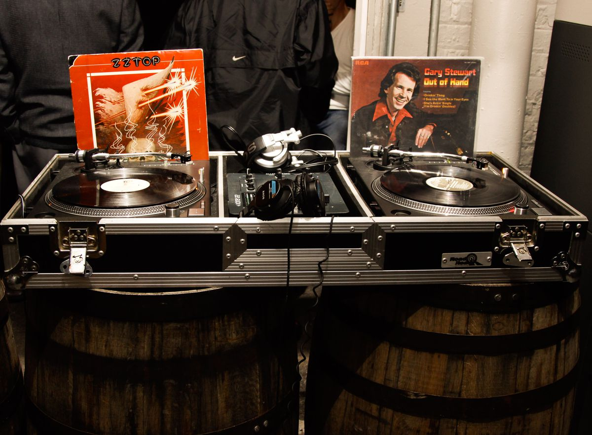 Two turntables and a mixer sit on a long metallic case on top of two barrels with two record sleeves resting in the back.
