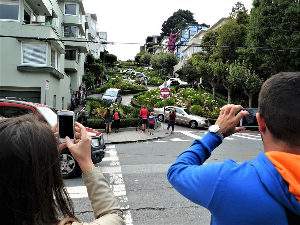 Cars winding down a hillside street with multiple sharp turns and switchbacks. In the foreground, people with phones in hand take photos of the traffic.