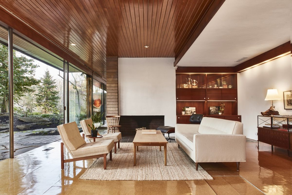 A midcentury modern living room with wood ceilings and floor-to-ceiling windows.